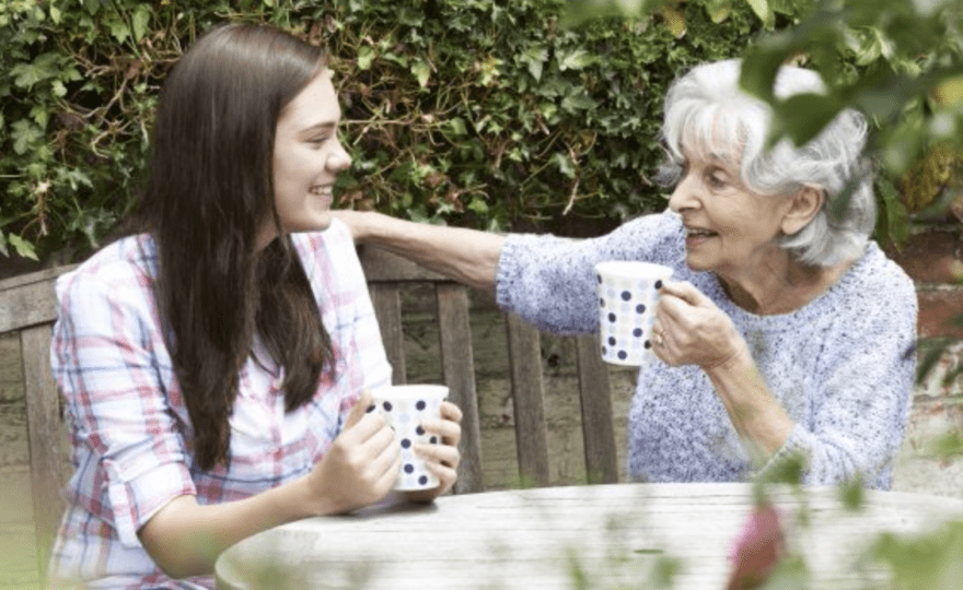 YOUNG FEMALE HAVING A CHAT WITH ELDERLY FEMALE SERVICE USER IN GARDEN